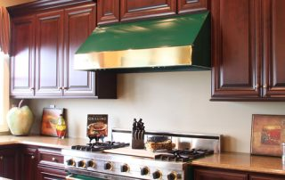 kitchen with dark wood cabinetry with green hood & range