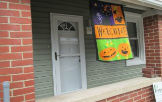 House with green siding & brick porch with halloween flag